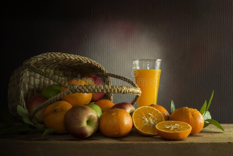 Molti generi di frutti in a in canestro di vimini e succo d'arancia sopra immagine stock libera da diritti