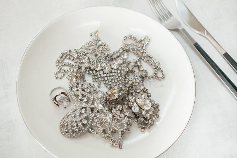 Molti gioielli artificiali scintillanti del diamante su un piatto con un coltello e una forcella Fine in su fotografia stock libera da diritti