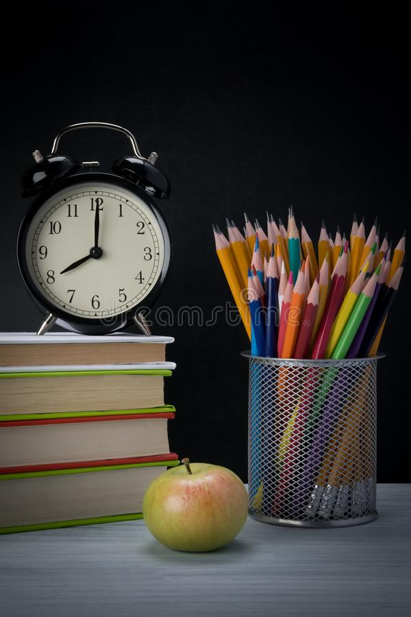 Molti libri per scuola, una sveglia e una tazza con le matite sullo scrittorio di scrittura immagini stock libere da diritti