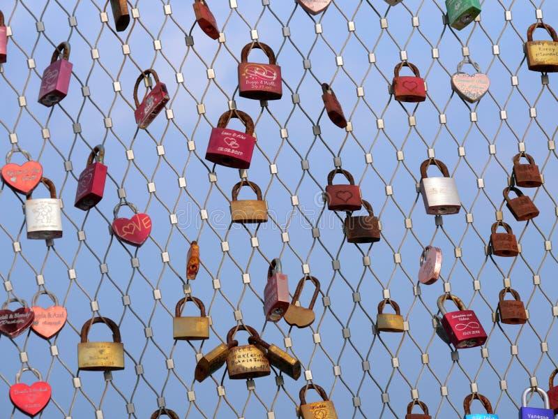 Molti lucchetti degli amanti che appendono sulle inferriate del ponte fotografia stock libera da diritti