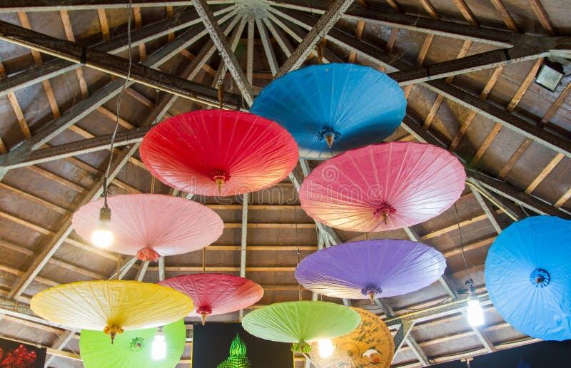 Molti ombrelli variopinti appendono sulle inferriate del ferro con fondo di legno fotografia stock libera da diritti