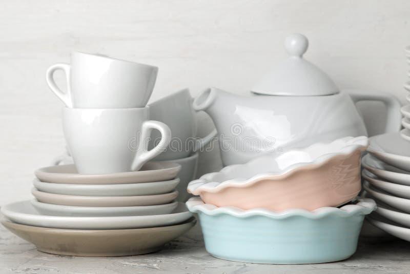 Molti piatti differenti dinnerware su un fondo del cemento leggero piatti per il servizio della tavola vari piatti, ciotole e Cu fotografie stock