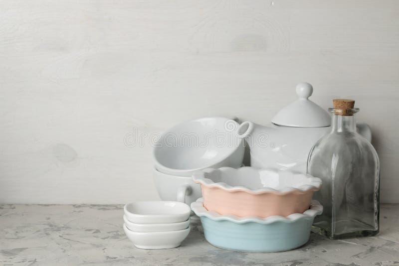 Molti piatti differenti dinnerware su un fondo del cemento leggero piatti per il servizio della tavola vari piatti, ciotole e Cu fotografia stock libera da diritti