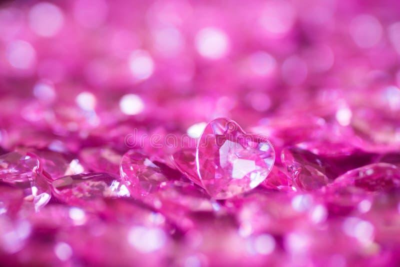 Molti piccoli cuori di cristallo rosa con il fondo del bokeh immagini stock libere da diritti