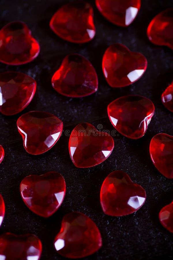 Molti piccoli cuori di cristallo rossi su fondo di legno nero fotografie stock