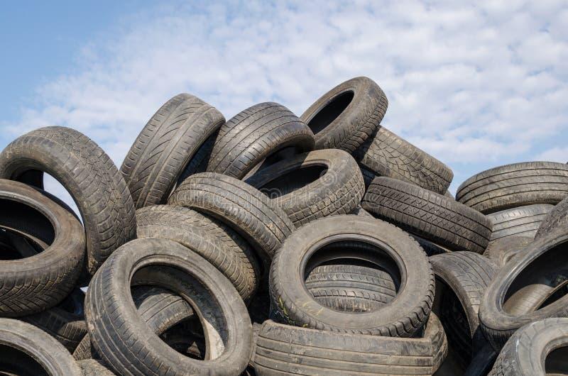 Molti pneumatici usati contro cielo blu con le nuvole bianche immagini stock libere da diritti