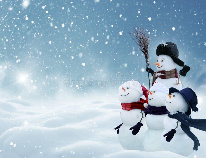 Molti pupazzi di neve che stanno nel paesaggio di Natale di inverno fotografie stock libere da diritti