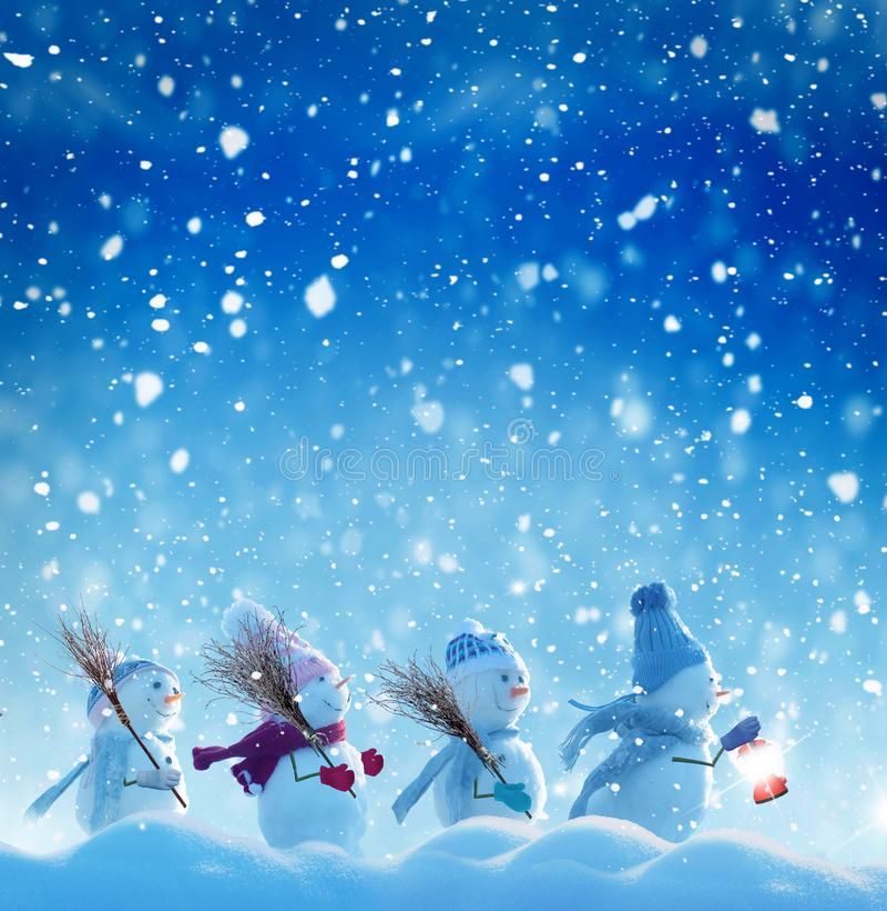 Molti pupazzi di neve che stanno nel paesaggio di Natale di inverno immagine stock libera da diritti