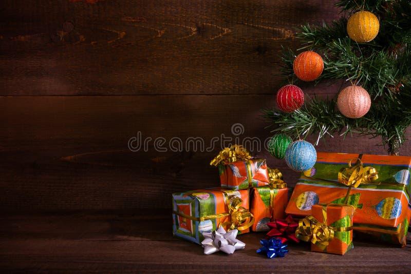 Molti regali di Natale sotto l'albero sul fondo della plancia fotografie stock