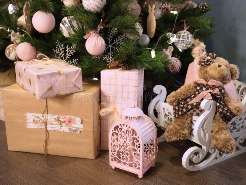 Molti regali di Natale sul pavimento su un fondo dell'albero di Natale fotografie stock