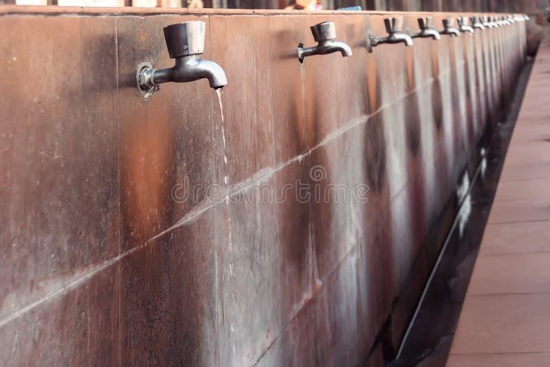 Molti rubinetti dell'acciaio con lo scorrimento dell'acqua potabile immagini stock libere da diritti