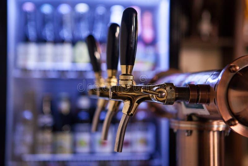 Molti rubinetti dorati della birra alla barra fotografia stock libera da diritti