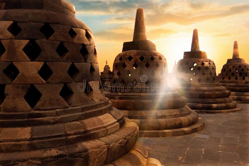 Molti stupas buddisti di pietra enormi contro lo sfondo dell'alba con i raggi di luce nel tempio di Borobudur Java Island In fotografia stock