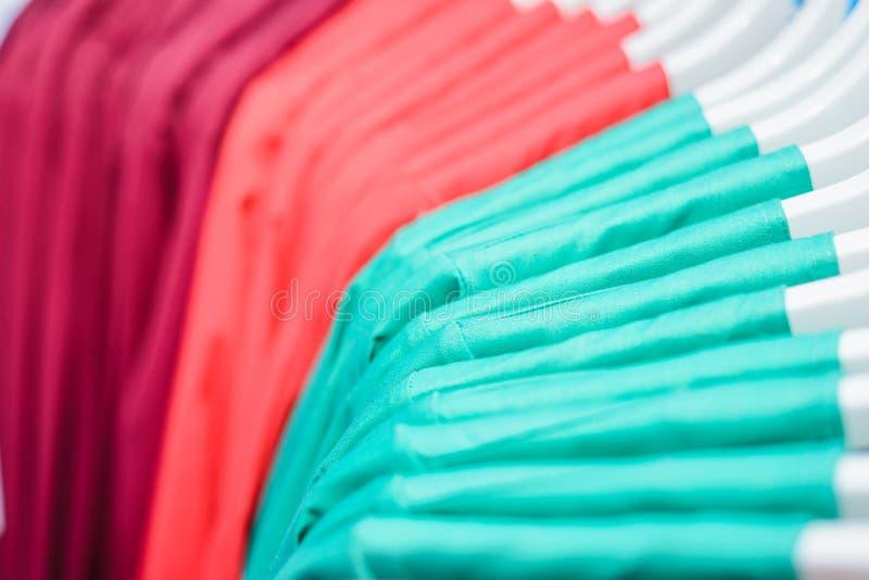Molti vestiti sui ganci fotografia stock