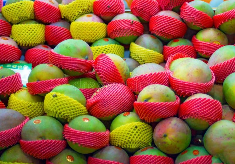Molto bella bugia del mango su un contatore della vetrina in pieno del mango verde e maturo immagini stock libere da diritti