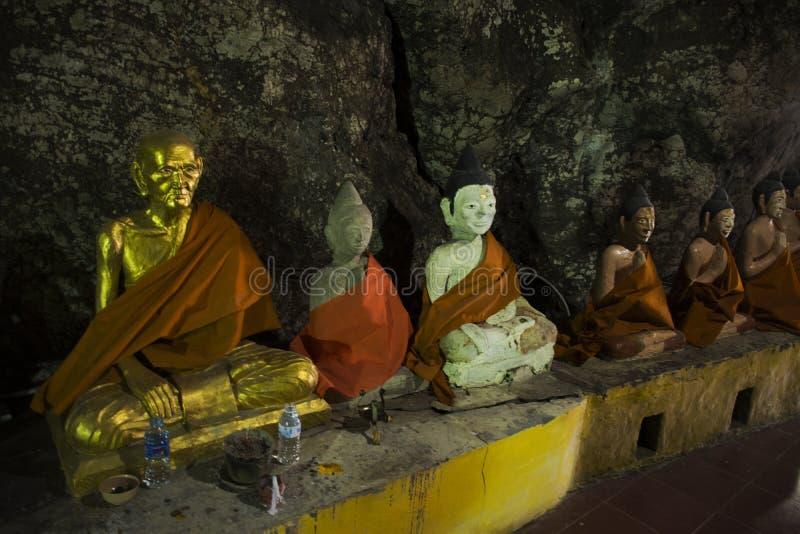 Molto Buddha e dio ed angelo e statua dell'eremita in caverna a Wat Khao Orr immagine stock