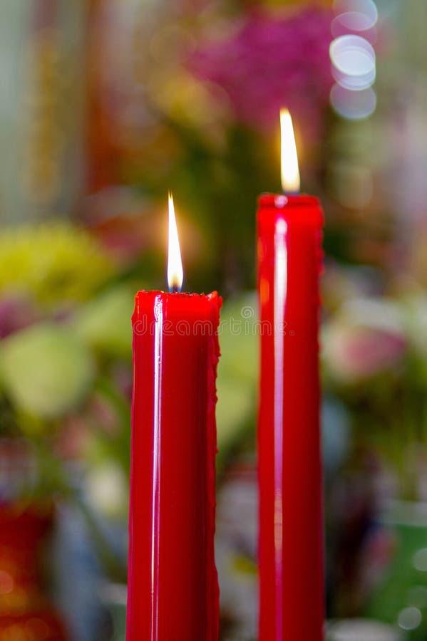 Molto combustione rossa, candele lunghe in tempio di budist immagine stock