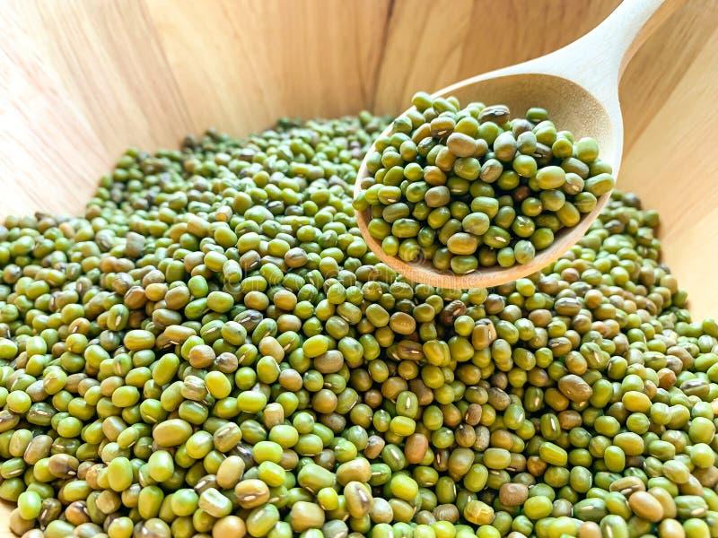 Molto fagiolo verde o fagiolini su un cucchiaio di legno in una ciotola di legno immagine stock libera da diritti