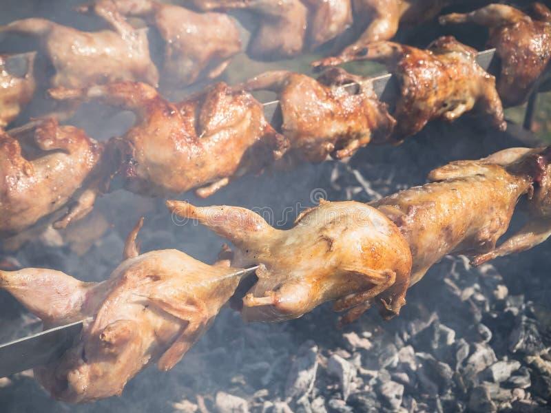 Molto pollo arrostito è arrostito su uno sputo nel fumo fotografia stock
