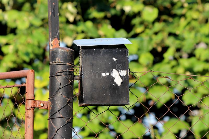 Molto - vecchia cassetta delle lettere nera usata del metallo con pittura incrinata montata sul palo parzialmente arrugginito con immagine stock