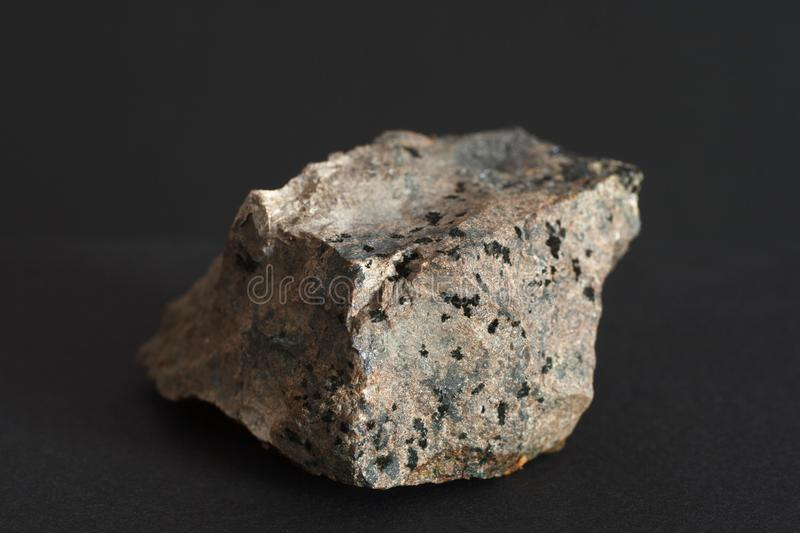 Molybdenite mineral on black background. Molybdenite mineral and molybdenum ore on black background potentially for economic and industrial market prices news stock photography