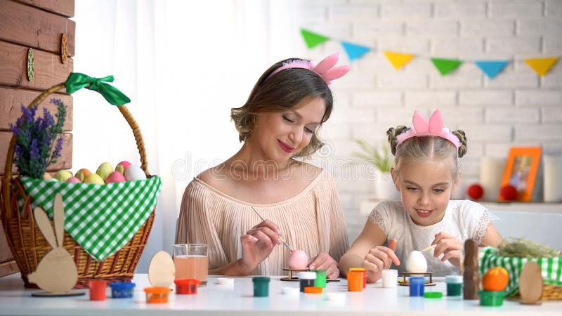 Mom και κορίτσι headbands που χρωματίζουν τα αυγά για Πάσχα, που αναπτύσσει τις ισχυρές σχέσεις στοκ φωτογραφίες