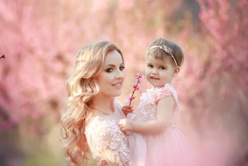 Mom με ένα νήπιο στη φυτεία με τριανταφυλλιές με τα δέντρα λουλουδιών στοκ φωτογραφίες