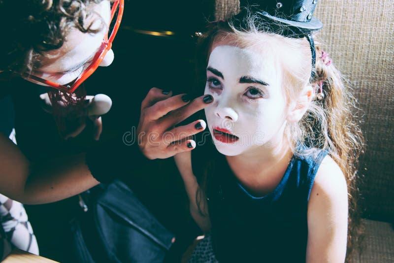 mom κάνει το μωρό της makeup mime στο εσωτερικό στοκ φωτογραφία