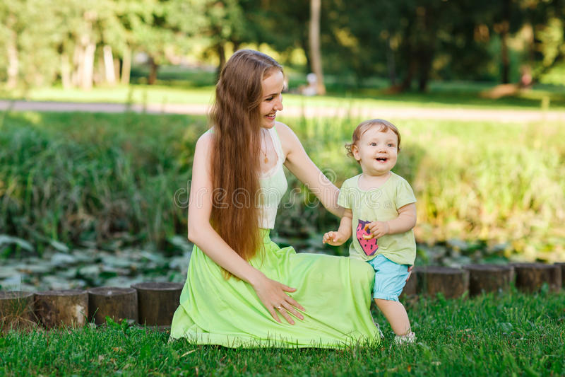 Mom και λίγη κόρη στο πάρκο στον πράσινο χορτοτάπητα στοκ φωτογραφία με δικαίωμα ελεύθερης χρήσης