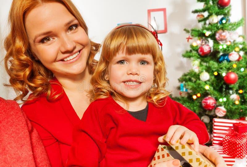 Mom και λίγη συνεδρίαση κορών από το χριστουγεννιάτικο δέντρο στοκ φωτογραφία με δικαίωμα ελεύθερης χρήσης
