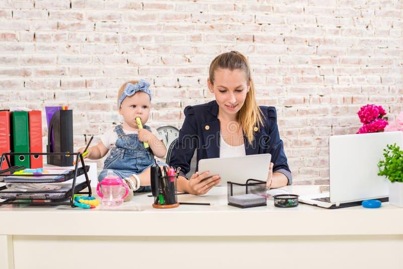 Mom και επιχειρηματίας που λειτουργούν με το φορητό προσωπικό υπολογιστή στο σπίτι και που παίζουν με το κοριτσάκι της στοκ φωτογραφία με δικαίωμα ελεύθερης χρήσης
