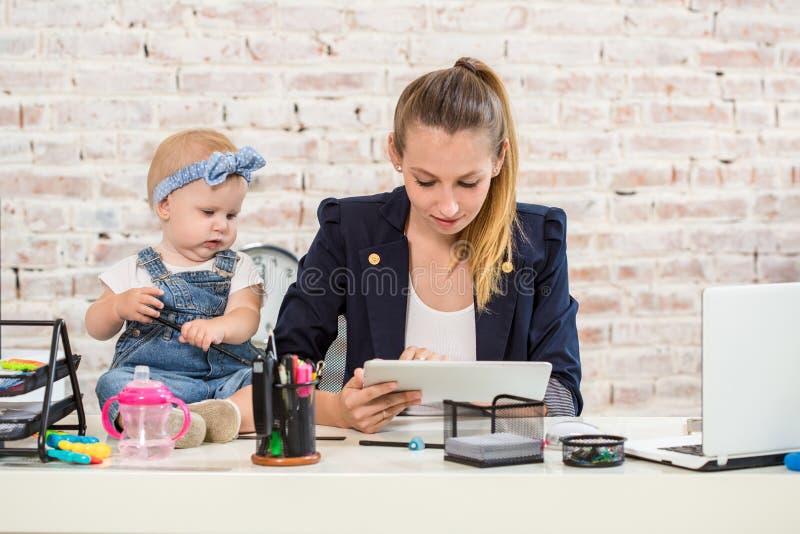 Mom και επιχειρηματίας που λειτουργούν με το φορητό προσωπικό υπολογιστή στο σπίτι και που παίζουν με το κοριτσάκι της στοκ εικόνες με δικαίωμα ελεύθερης χρήσης