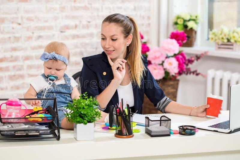 Mom και επιχειρηματίας που λειτουργούν με το φορητό προσωπικό υπολογιστή στο σπίτι και που παίζουν με το κοριτσάκι της στοκ εικόνες