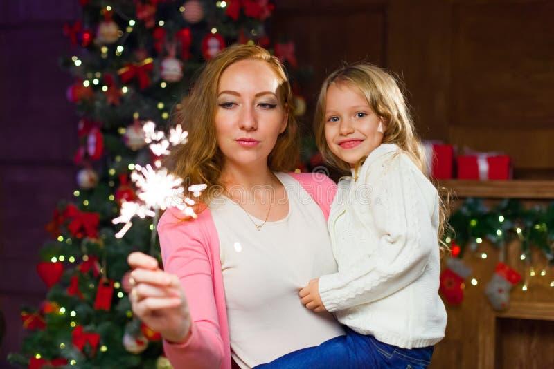 Mom και κόρη που έχουν τη διασκέδαση σε έναν νέο εορτασμό έτους ` s, κράτημα στοκ φωτογραφία με δικαίωμα ελεύθερης χρήσης