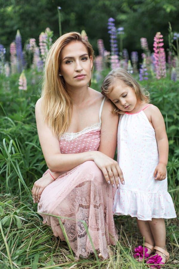 Mom και κόρη σε έναν ανθίζοντας κήπο στο καλοκαίρι στοκ φωτογραφίες με δικαίωμα ελεύθερης χρήσης