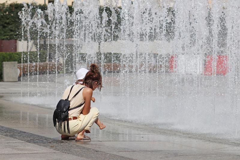Mom και το παιδί κοντά στους αναζωογονώντας παφλασμούς της πηγής θερινών πόλεων Λούσιμο και υπόλοιπο στο ελεύθερο χρόνο σας στις  στοκ εικόνα
