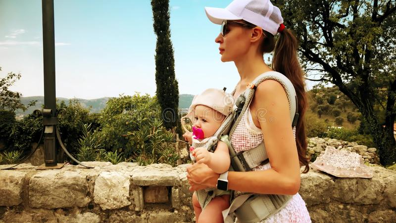 Mom και το παιδί της που ταξιδεύουν με το σακίδιο πλάτης μεταφορέων μωρών στις διακοπές στοκ εικόνες