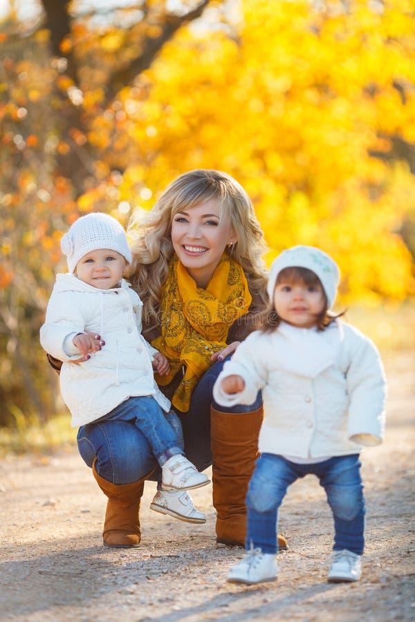 Mom και δύο μικρά κορίτσια που περπατούν στο πάρκο το φθινόπωρο στοκ εικόνα