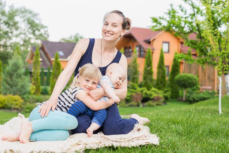 Mom με τα παιδιά που κάθονται σε έναν πράσινο χορτοτάπητα χλόης στο πάρκο Νέα μητέρα με την κόρη και το γιο που έχουν τη διασκέδα στοκ εικόνα
