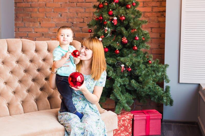 Mom με το παιχνίδι παιδιών στο βράδυ Χριστουγέννων, χειμερινά Σαββατοκύριακα, άνετη σκηνή στοκ φωτογραφία