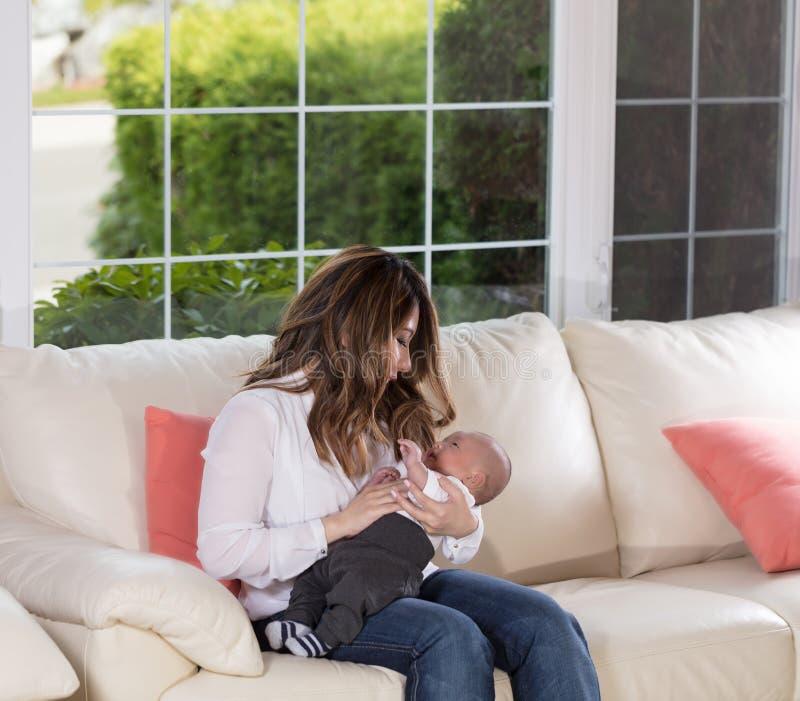 Mom που κρατά το γιο νηπίων της στον άσπρο καναπέ στοκ φωτογραφίες