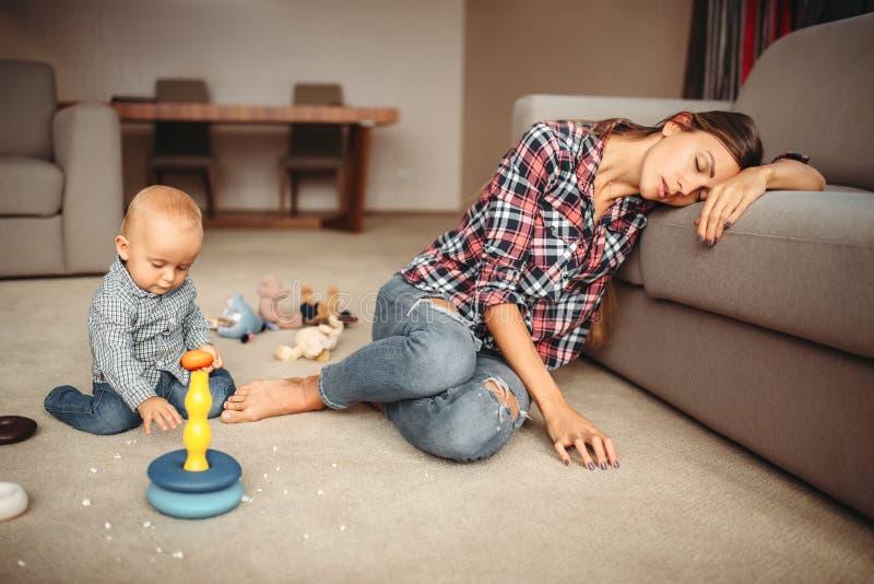 Παιχνίδι παιδάκι στο πάτωμα, ύπνοι μητέρων στοκ εικόνα με δικαίωμα ελεύθερης χρήσης