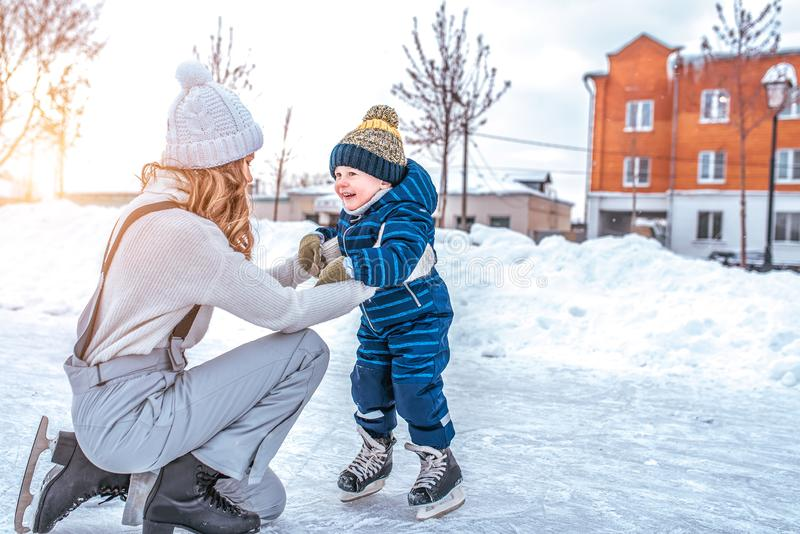 Mom with baby boy 3-5 years old, learn to train, ride in winter city on rink, ice skating. Happy smiling children play stock photo