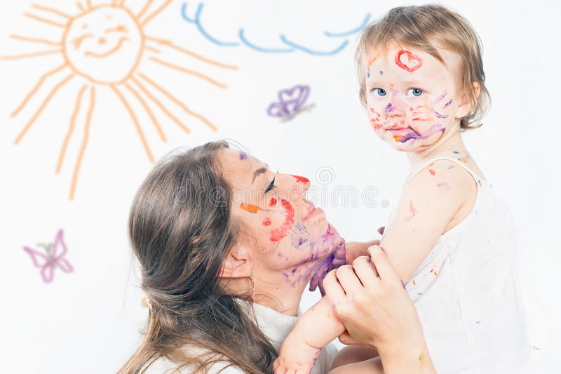 Mom and baby draws with colored inks paint. Games with child affect early development. Important to spend enough time with your kids stock image