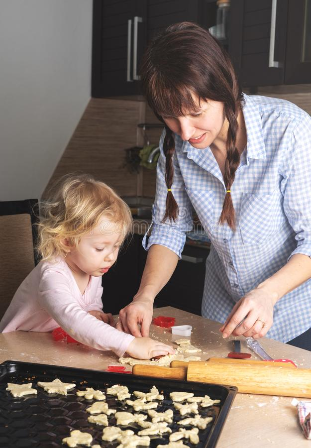 Mom and baby are engaged in baking cookies at home in her kitchen. Not staged fragment from real life. royalty free stock photography