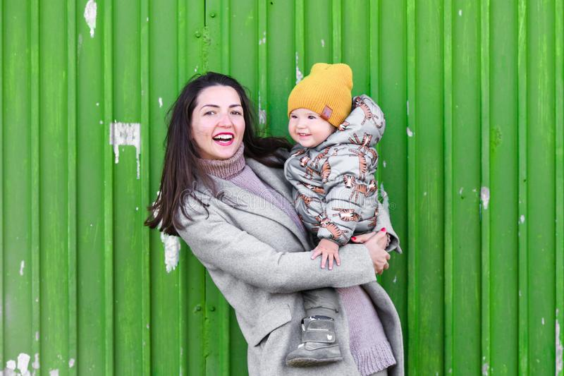 Mom with a baby on a green background. In a warm gray coat. Portrait of a beautiful girl with her son on a green background. Holds. A one-year-old child in his royalty free stock image