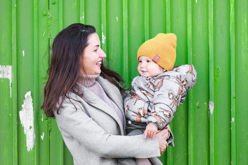 Mom with a baby on a green background. In a warm gray coat. Portrait of a beautiful girl with her son on a green background. Holds. A one-year-old child in his royalty free stock images