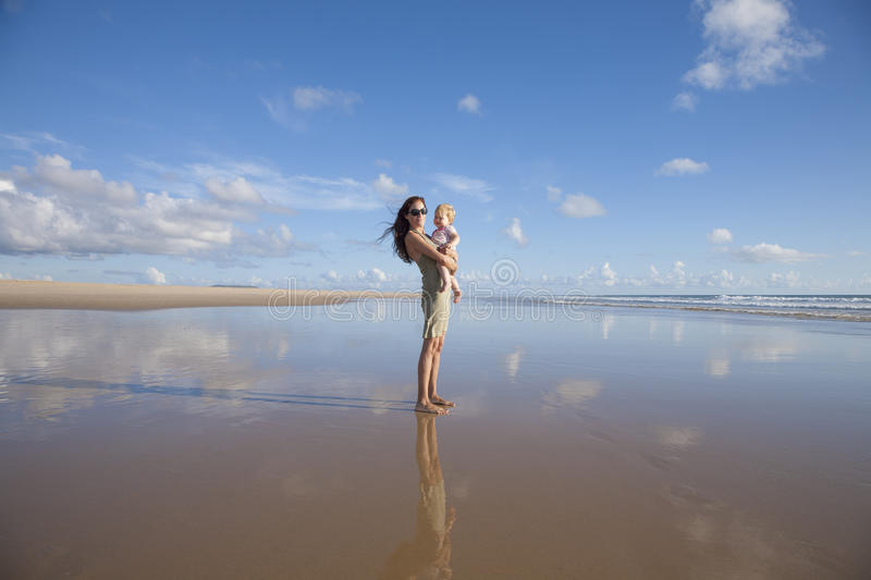 Mom with baby at lonely beach stock photography