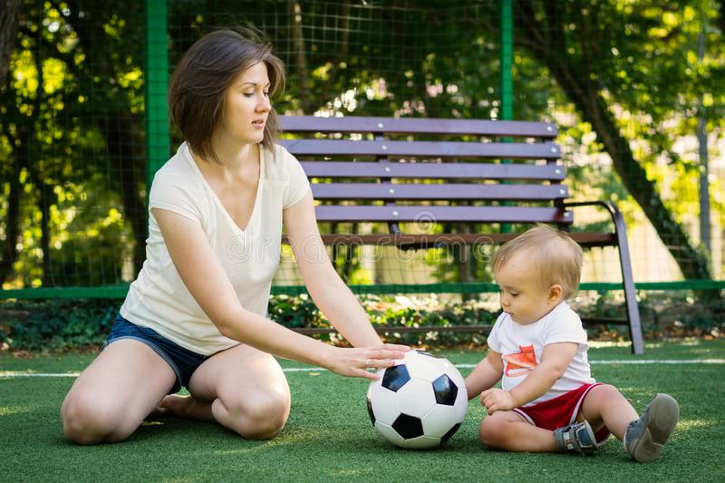 Mom and baby roll soccer ball to each other sitting at football field. Mother and son playing together. Summer family fun outdoors stock photography
