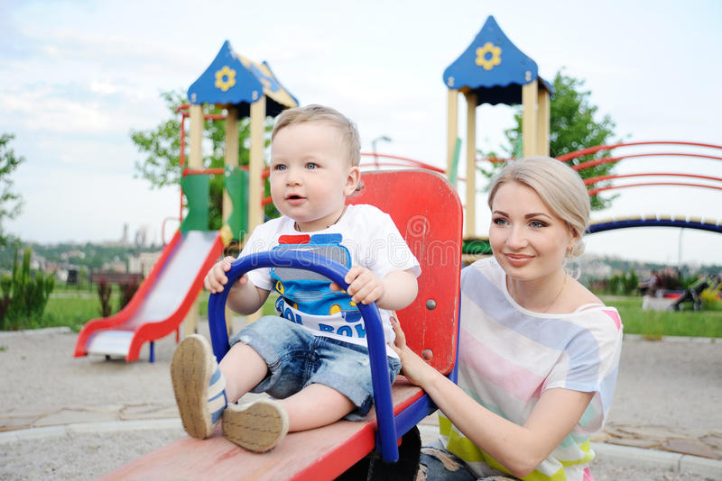 Mom and baby son play in the playground stock photography